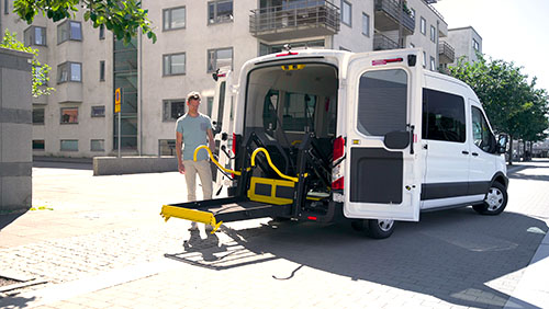 Man standing at the rear of a van, operating an E-Series wheelchair lift