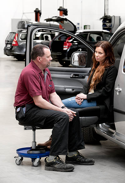 Technician talking to a customer sitting in a car seat.