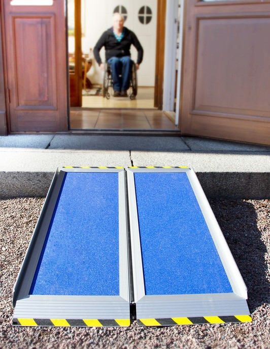 A wheelchair ramp leading up a step into a house, a man in the back moving towards the door.