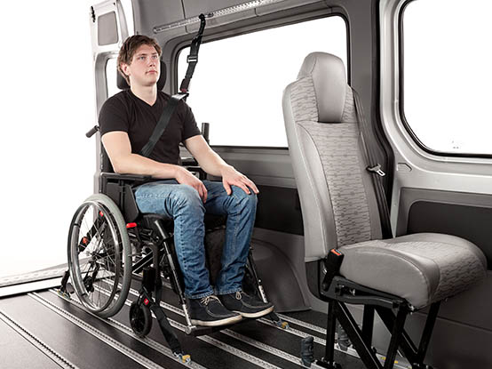 Person seated in a wheelchair with occupant and wheelchair restraints