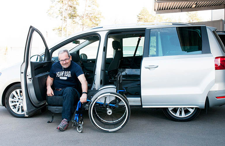 Man getting in to a van from a wheelchair