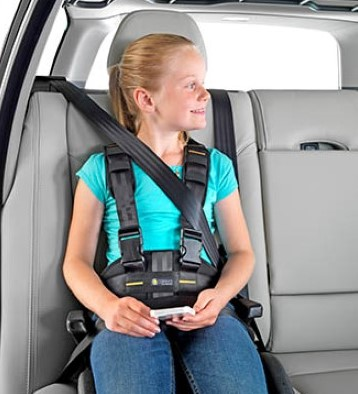 Girl sitting in a car with a posture belt strapped on