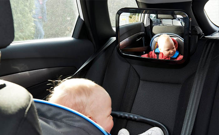 Baby sitting in a car looking into a mirror