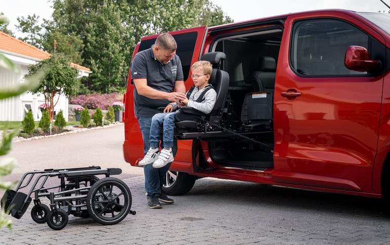 Man assisting a child into a turnign seat