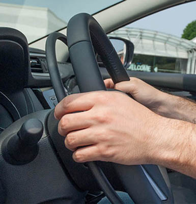 Hands holding a steering wheel with a gas ring.
