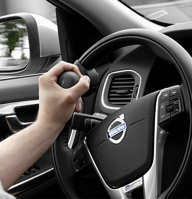 One hand holding a steering wheel by the steering device.