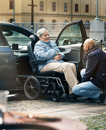 Man assissting women transfer from wheelchair into car with a Carony