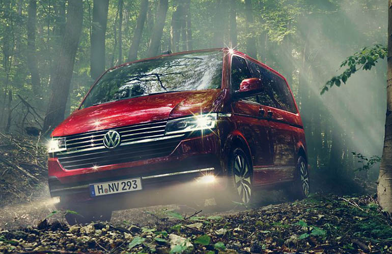 Red Volkswagen multivan in a forest
