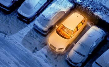 Aerial view of cars covered in snow and one car heated without snow