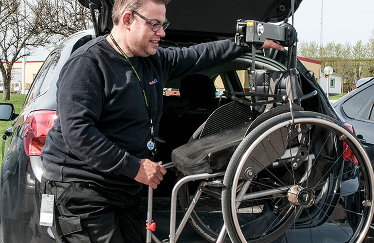 Man using a wheelchair hoist to stow a wheelchair in the car booth