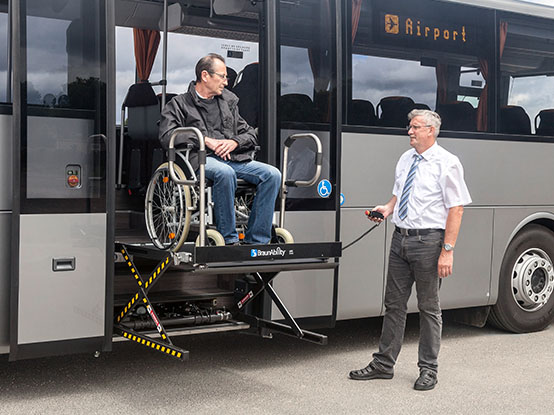 Bus driver assistint a man on a wheelchair into a bus by using a UVL lift