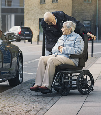 Man standing slightly behind woman on wheelchair and smiling  at her