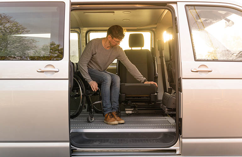 Van with a lateral door open, inside there is a man transfering from the wheelchair to the Turny 6 way