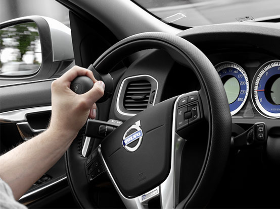 Close up of a hand holding a steering knob installed in a car
