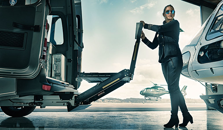 Woman in a flight hangar folding a lift installed in the back of a van