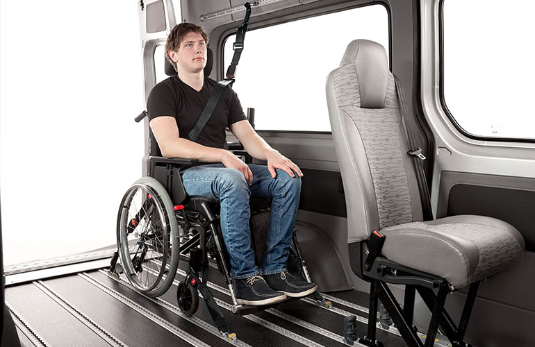 Interior view of a van where a young man seated in a wheelchair wears an occupant restraint and the wheelchair is anchored with tie-downs.