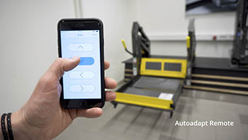 The BraunAbility Remote smartphone app with a wheelchair lift in the background