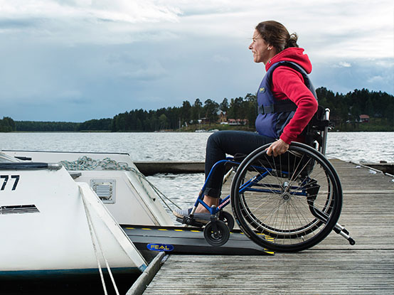 Woman on a wheelchair rolling over a ramp to get into a boat
