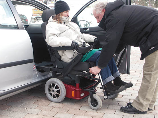 Man helping a woman get into the car with the help of a Carony Go