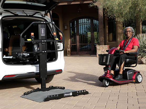 Woman driving her electric wheelchair onto a Joey Lift installed in a car