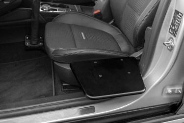 The BraunAbility Transfer Board next to the driver's seat of a car.