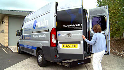 Woman opening the rear dorrs of a van, revealing a wheelchair lift