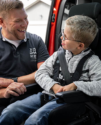Man smiling at young boy inside a car