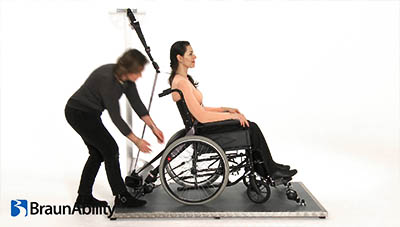 Woman sitting on a wheelchair being secured with tie-downs