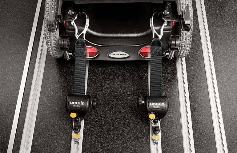 Rear view of a power chair held in place with tie-downs.
