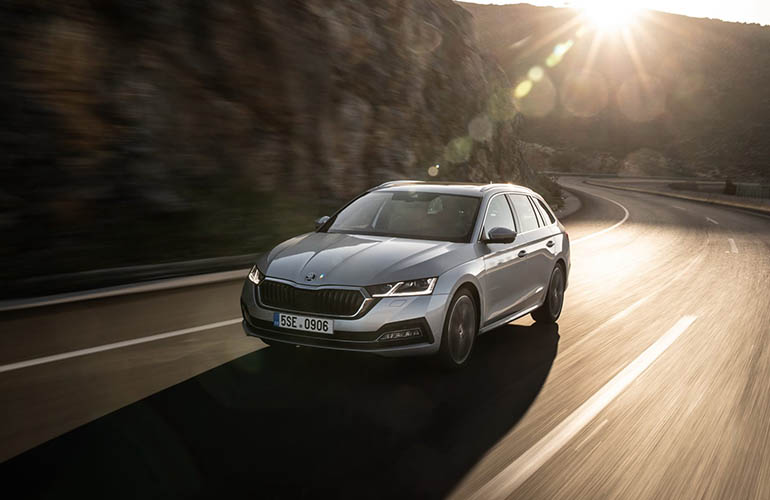 Grey Renault Talisman driving on a road by the water