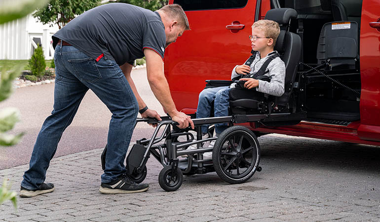 Child in Carony wheelchair transfer to car