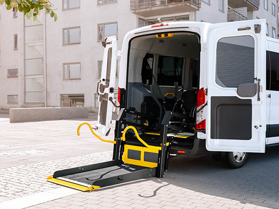 A van with open rear doors and a deployed wheelchair lift.