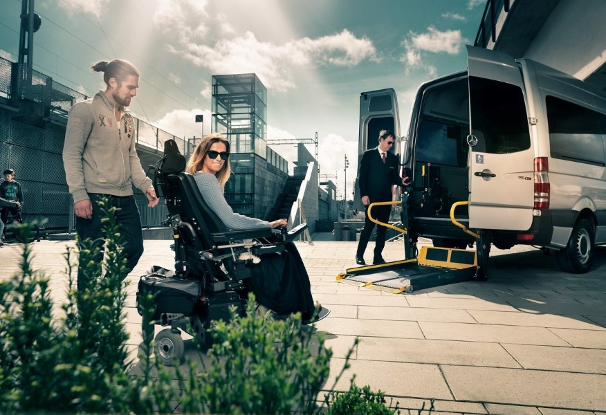 Woman in wheelchair about to enter a van using a wheelchair lift