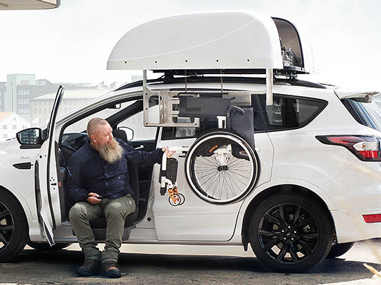 Man sitting in a white car retrieving a wheelchair from the top of the car with a chair topper