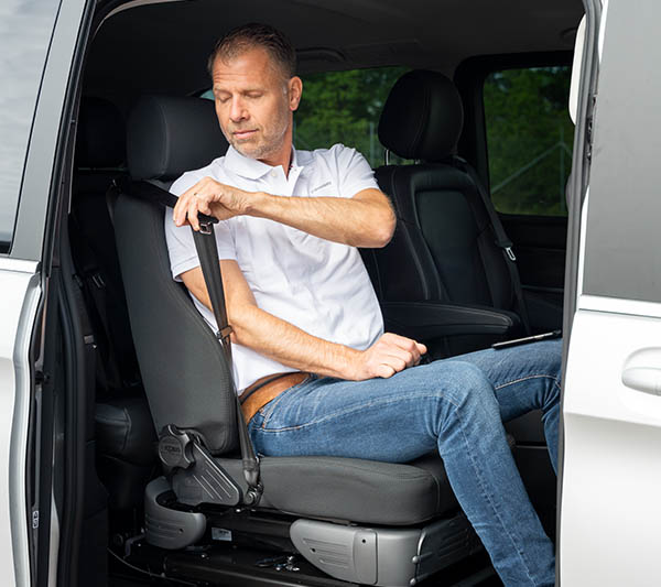 Man in the process of putting on a seat belt.