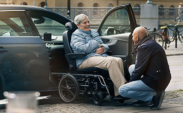 Picture of a man assisting a woman on a wheelchair into a car with the help of a Carony