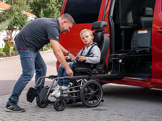 Man assisting boy transfer from wheelchair into car