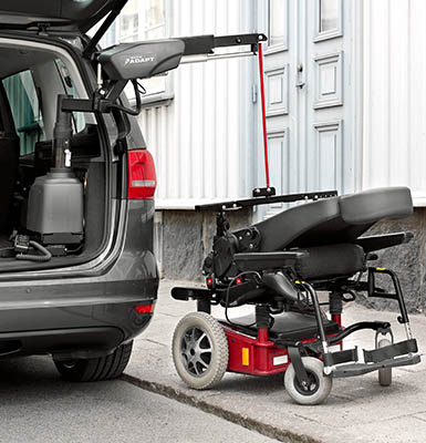 A powerchair ready to be loaded into a car using a hoist.