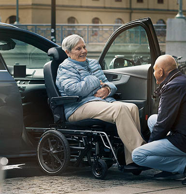 An elderly couple using a transfer wheelchair.