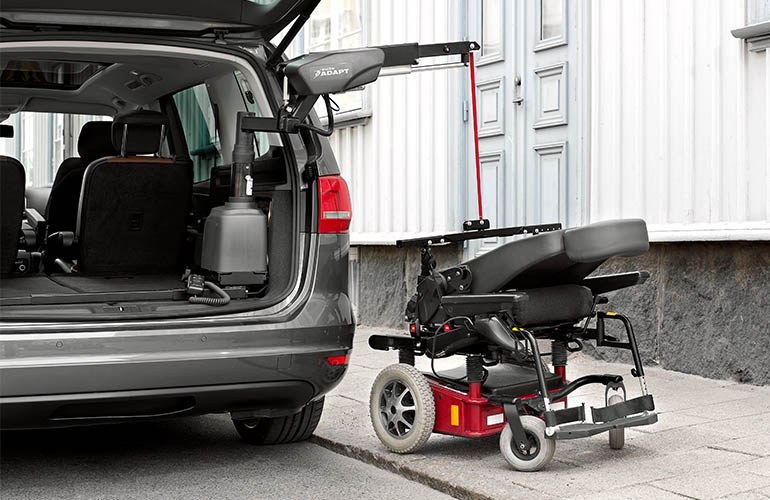 A powered wheelchair being lifted into a car with a Carolift 6900